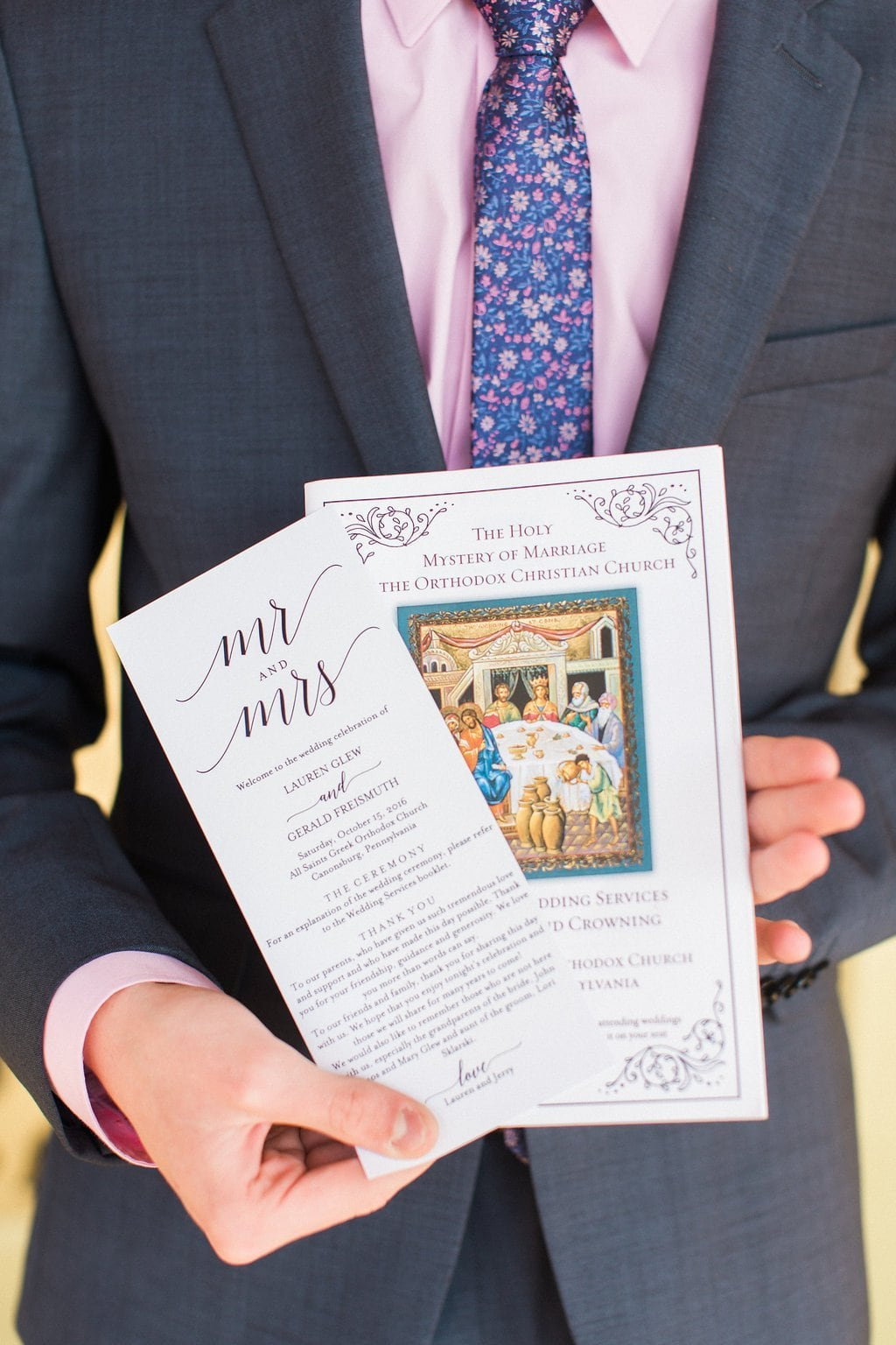 Wedding Programs held by a groomsman before the wedding ceremony