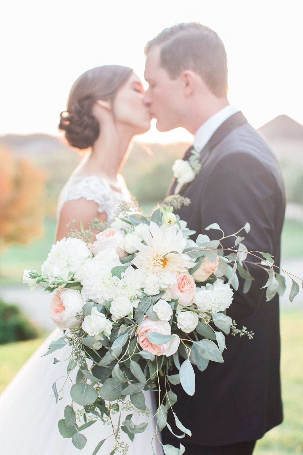 Gorgeous and romantic sunset portrait of the bride and groom with pink and white bouquet at the Club at Nevillewood