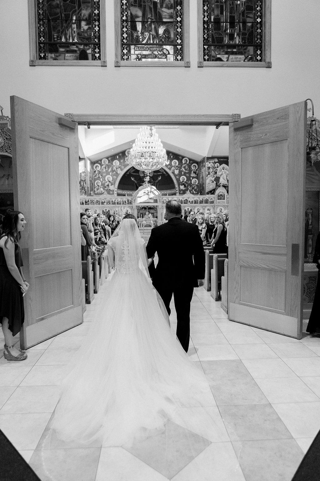 The back of the bride entering into the church with her father black and white photograph