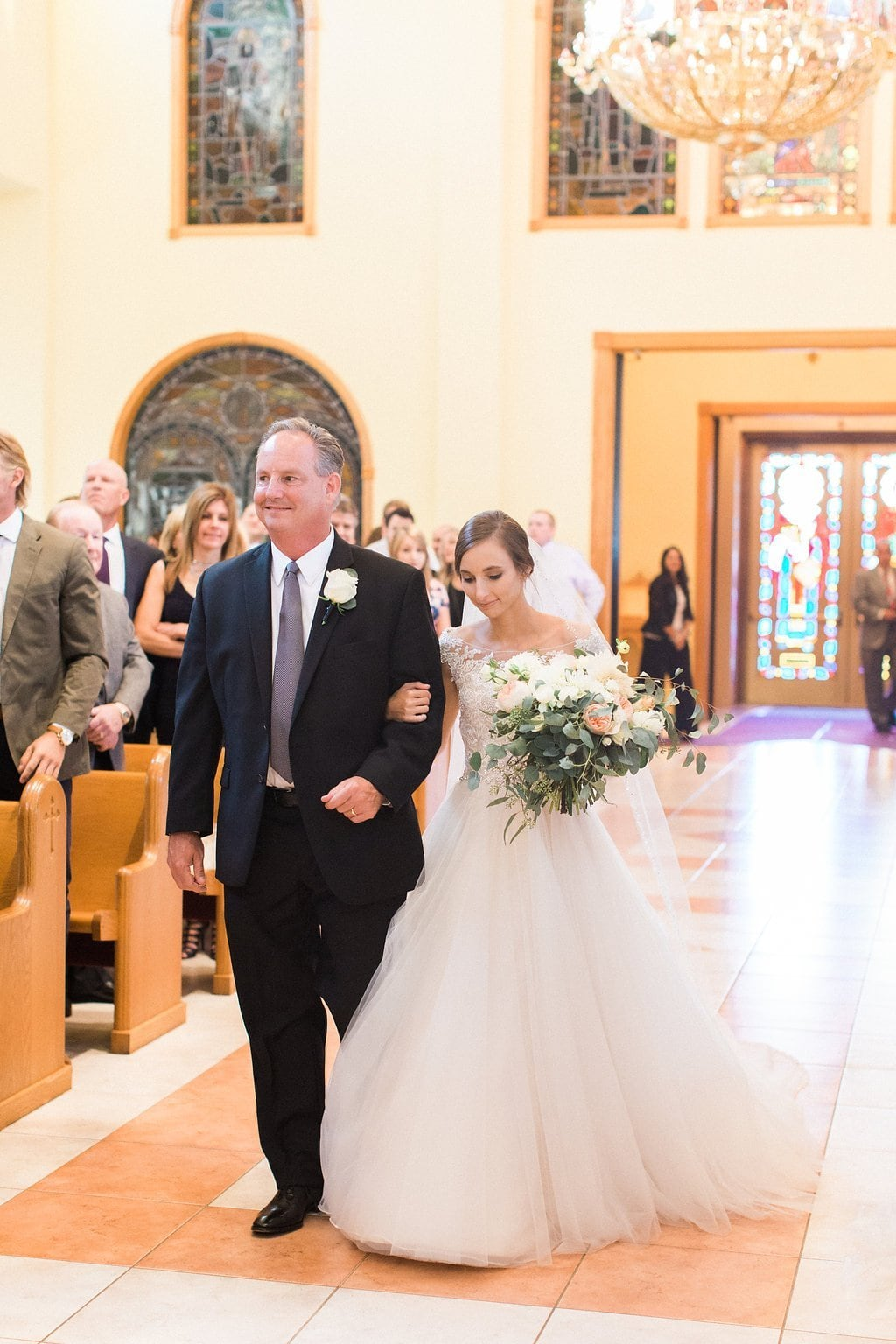 The bride walking down the isle with her father
