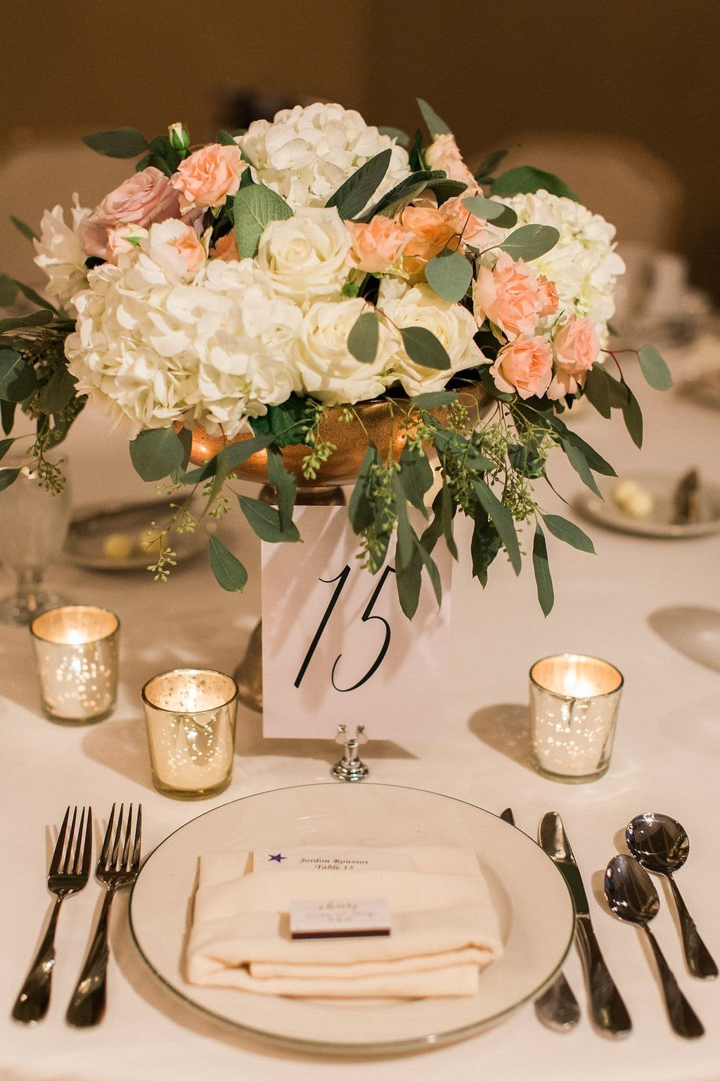 Table decorations and place setting details at the wedding reception with flowers candles and silverware