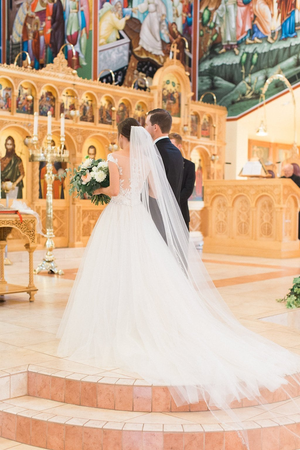 The bride and groom walking up to the alter at the All Saints Greek Orthodox Church