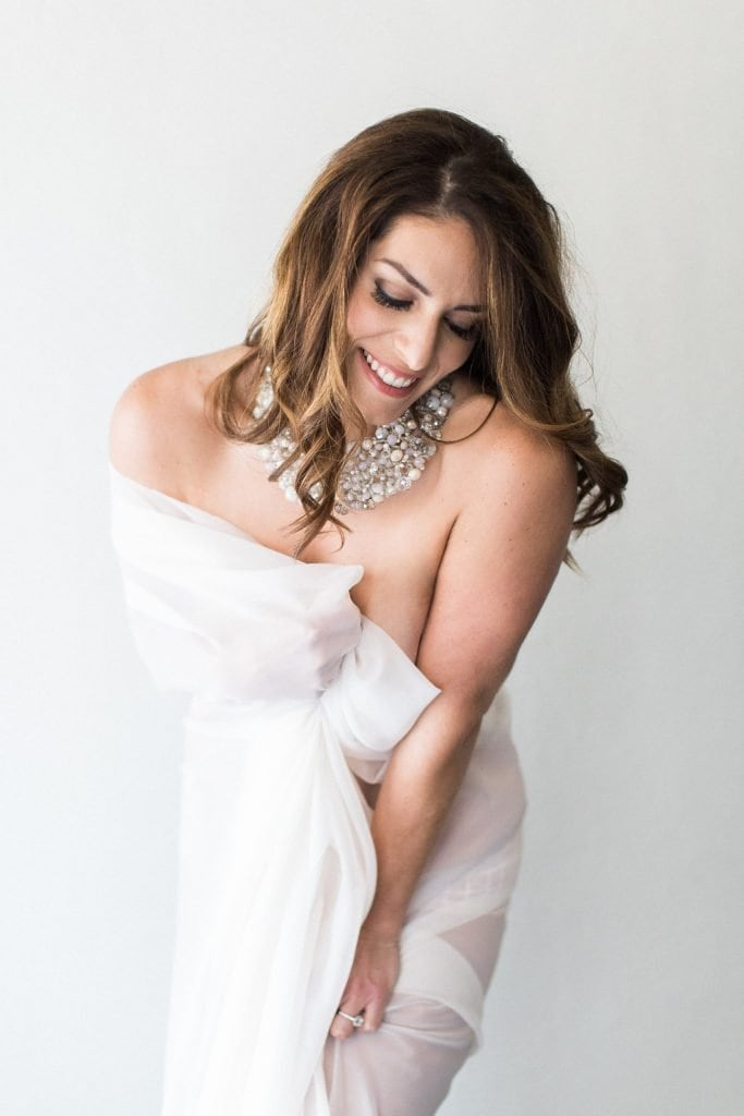 Fine art bridal boudoir in studio with model covered in white sheer fabric and laughing: Pittsburgh Boudoir Photography
