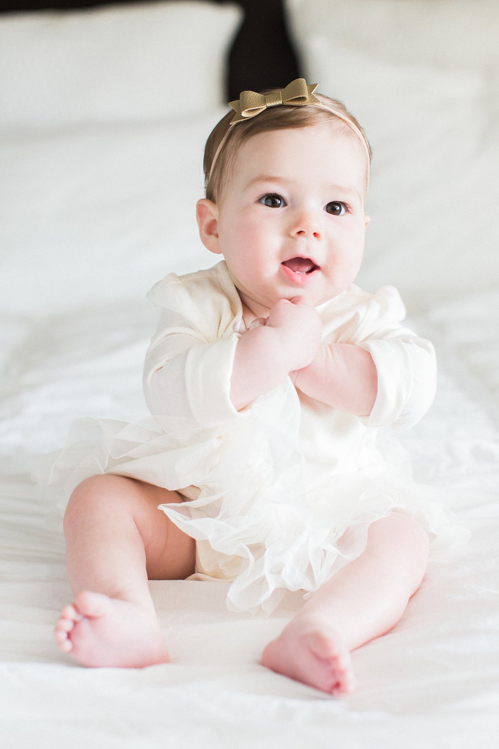 Baby clapping her hands and posing in a white dress with gold bow in her hair