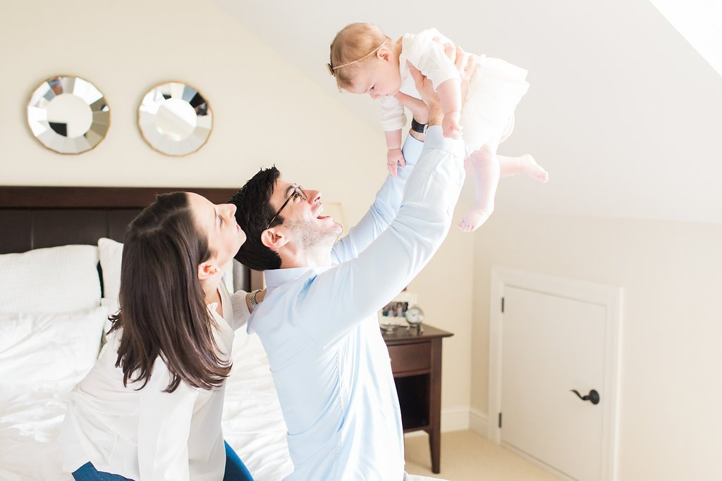 Dad holding baby in the air and mom smiling in their bedroom for family portraits