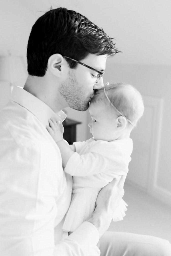 Dad kissing baby on the head for a sweet moment black and white photo