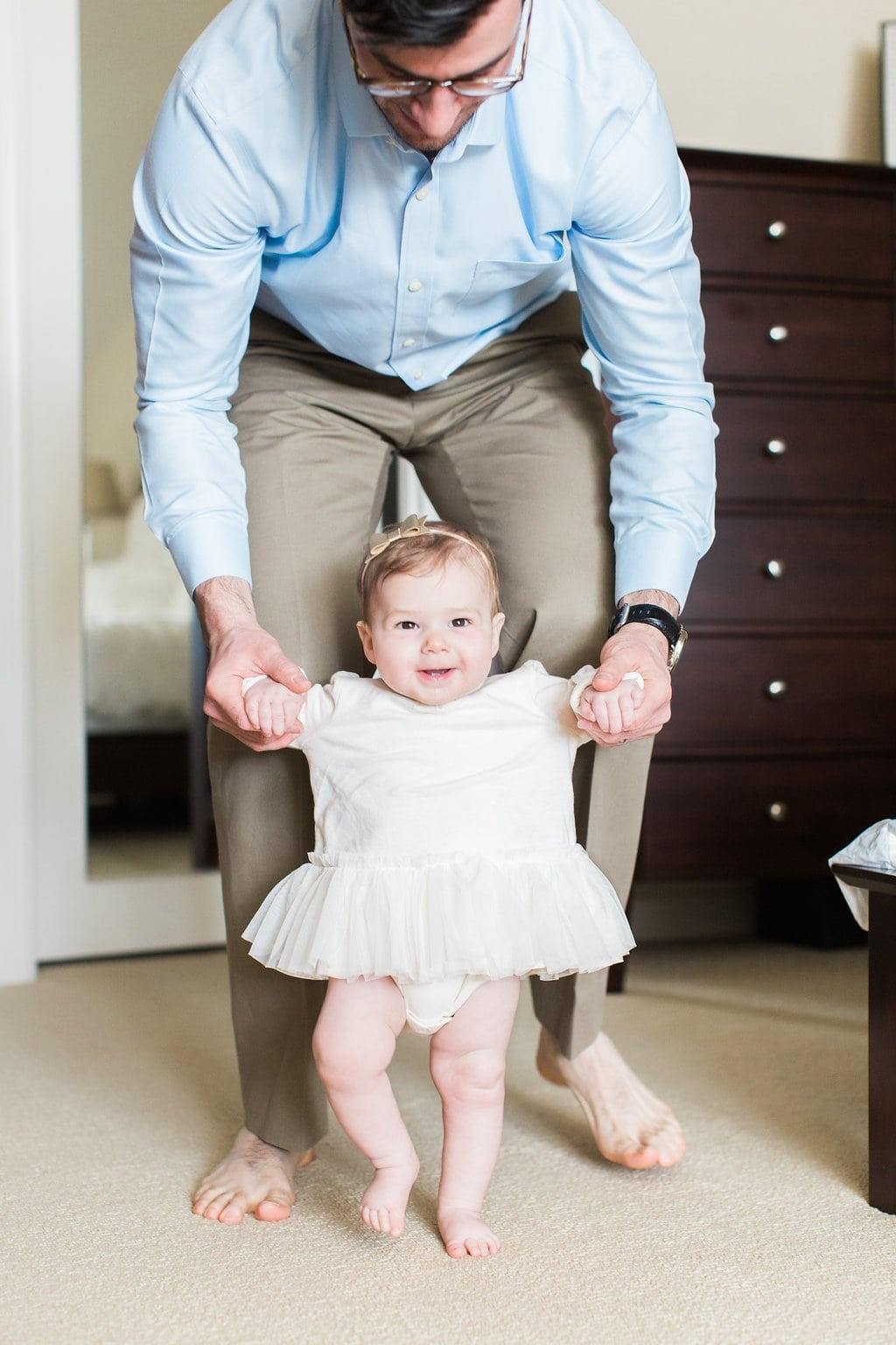 Father walking his baby daughter around the room during in-home lifestyle family photography session