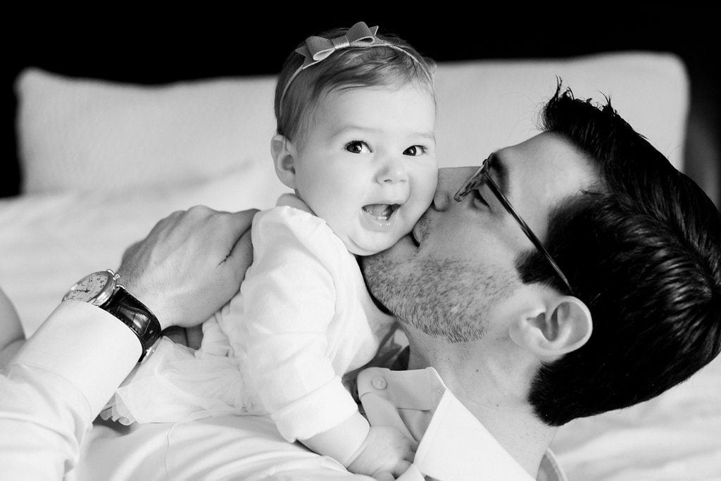 Dad kissing his daughter on the cheek and baby smiles during in home family photos black and white