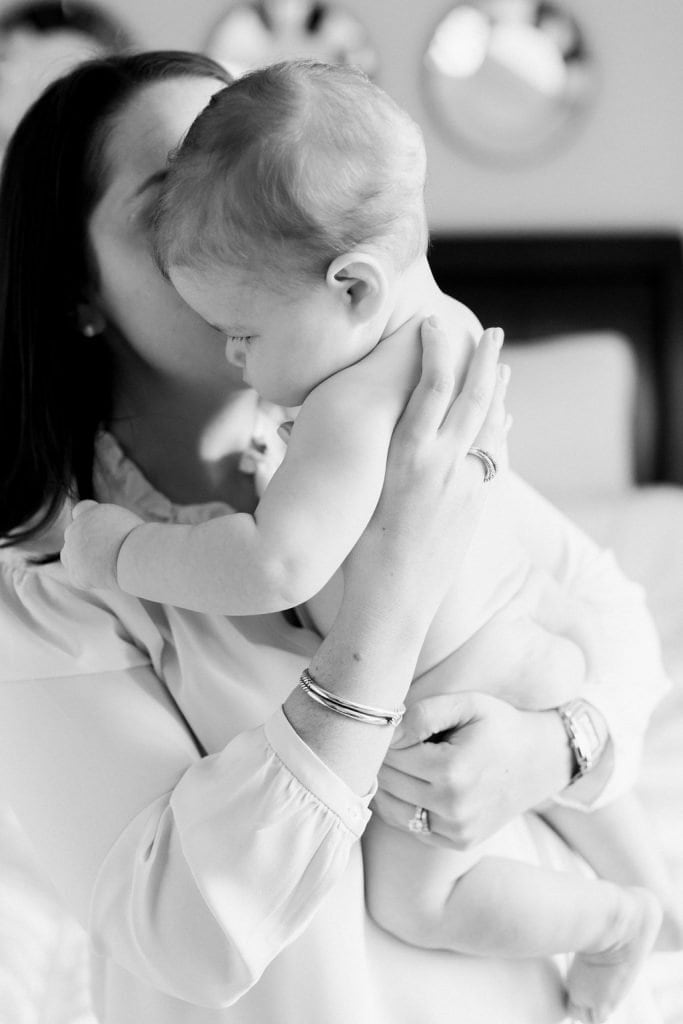Mom kissing baby on the cheek in a black and white photograph