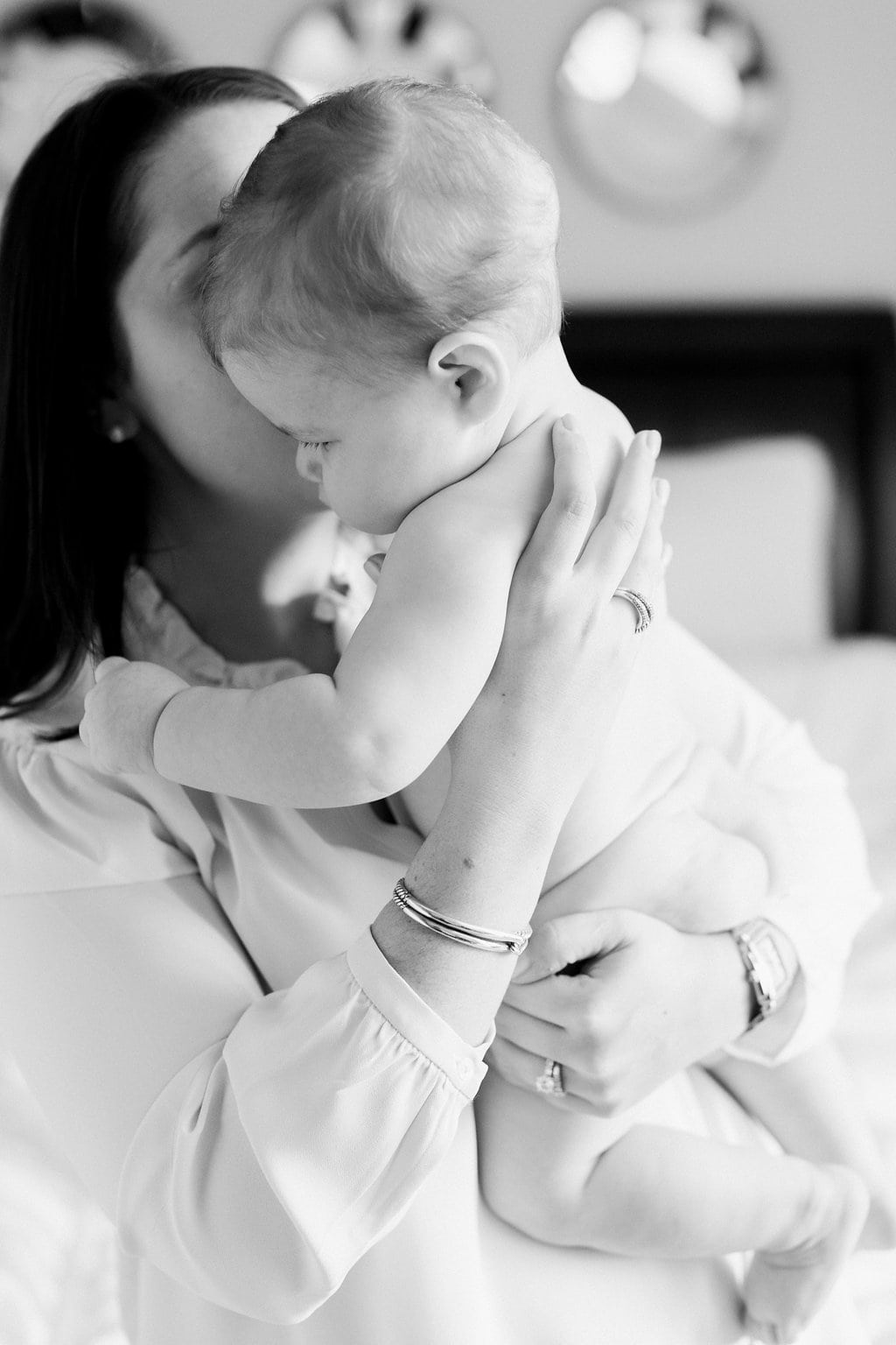 Mom kissing baby on the cheek in a black and white photograph during in-home lifestyle family photography session