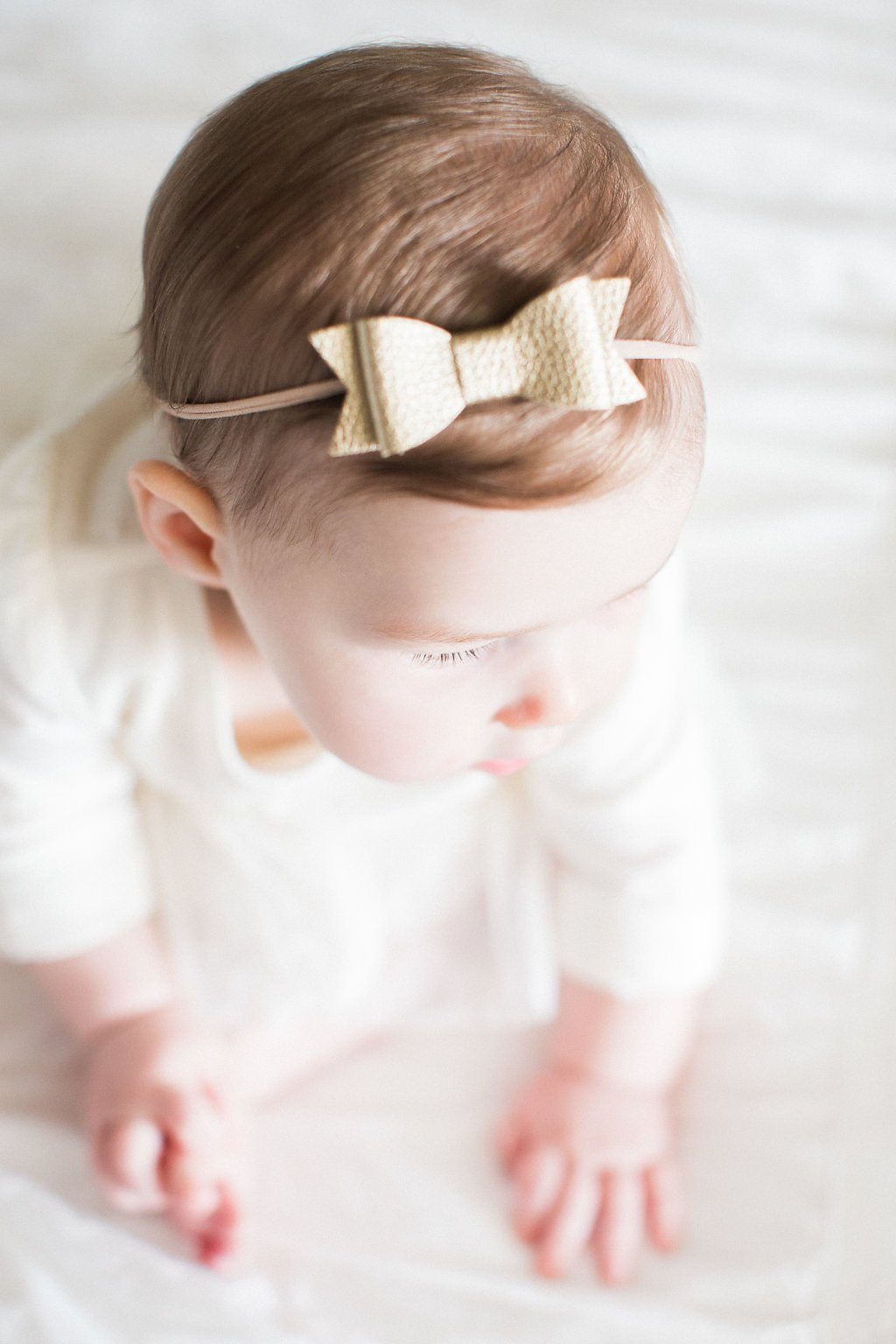Photograph of a gold bow in baby's hair during in-home lifestyle family photography session