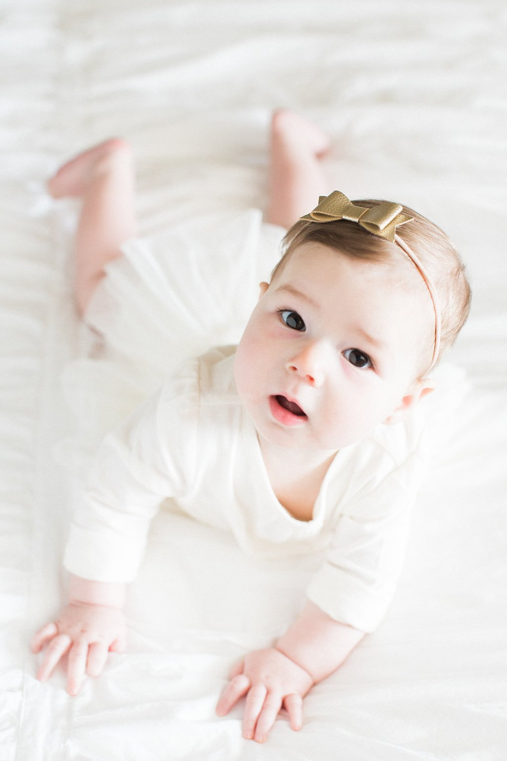 Photo of baby lying on a bed in a white dress with a gold bow in her hair