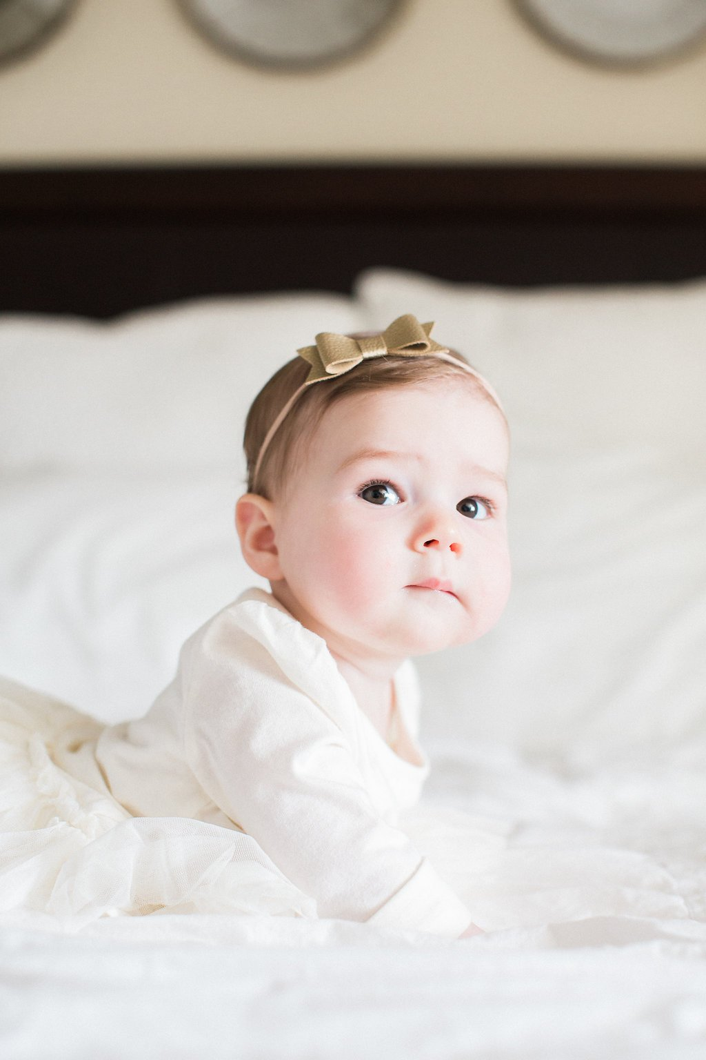 Picture of baby on a bed with white sheets in a white dress with a gold bow