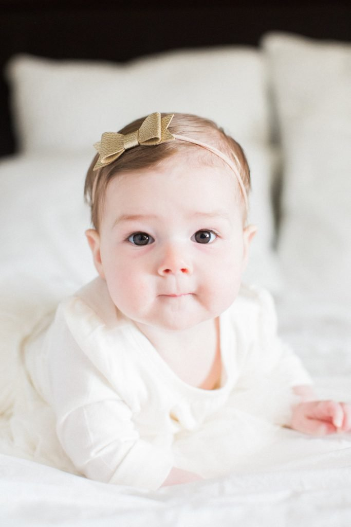 Portrait of baby on a bed in white dress with gold bow
