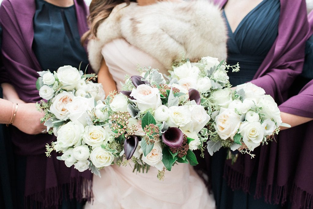 close up photo of bride with bridesmaids and bouquets of white and purple flowers