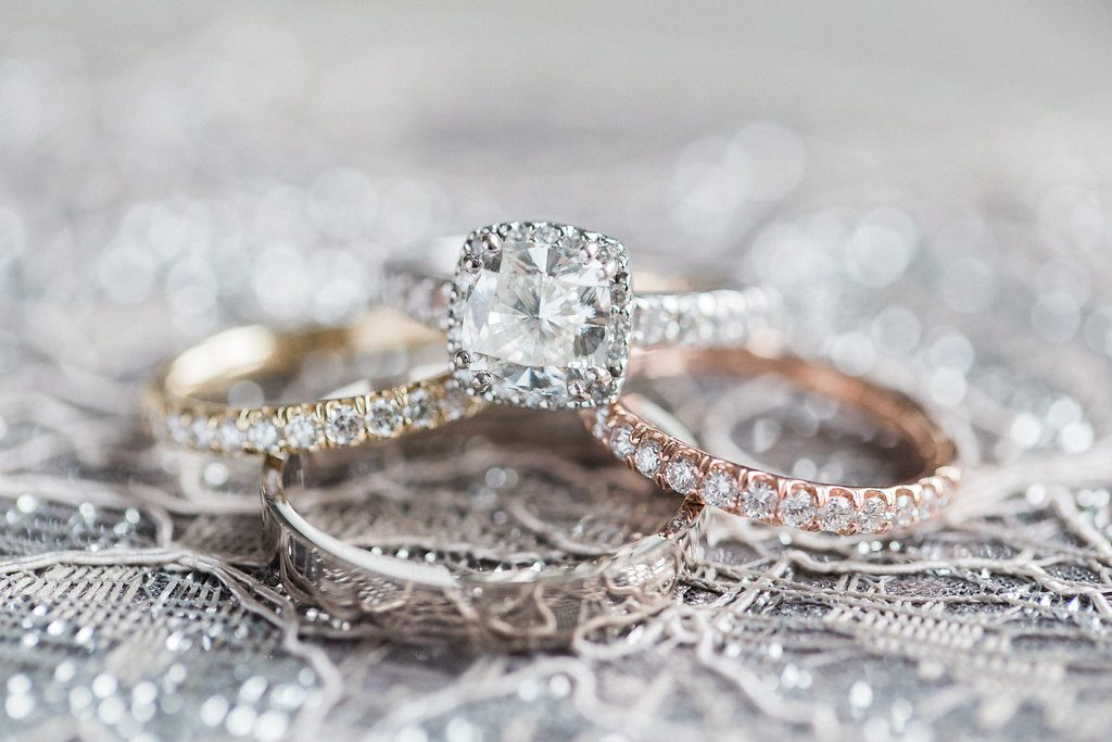 Close of photo of the engagement ring and wedding bands rose gold and silver