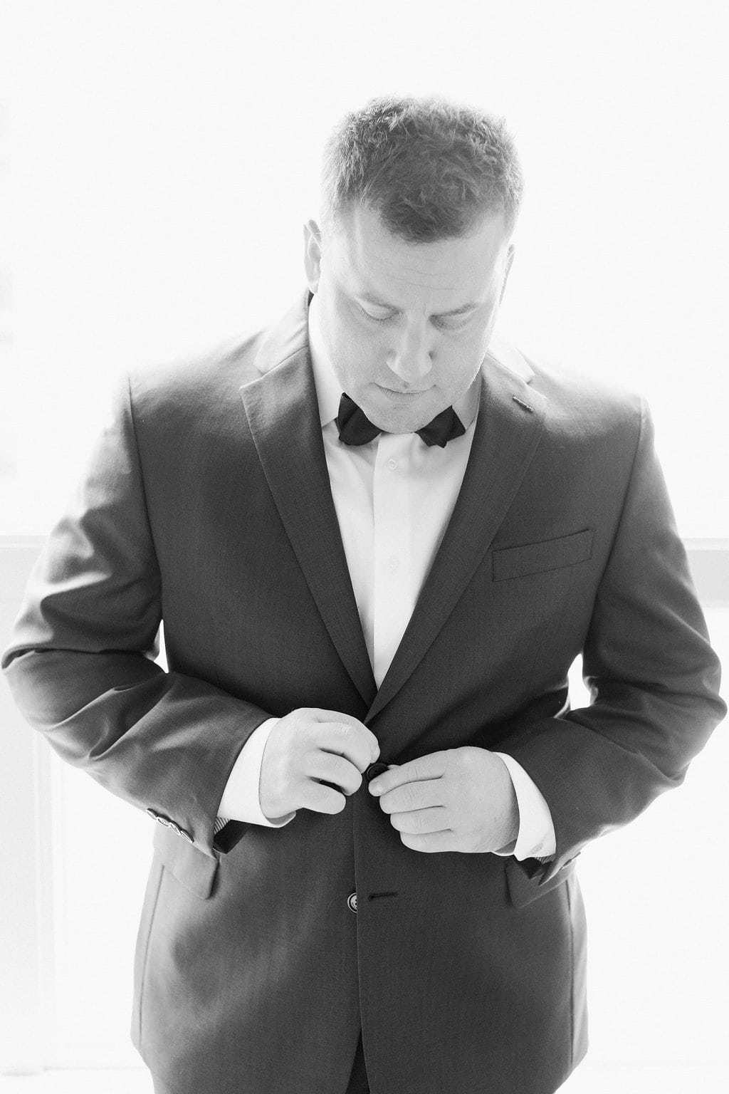 Groom buttoning up and getting dressed in his suit at the hotel