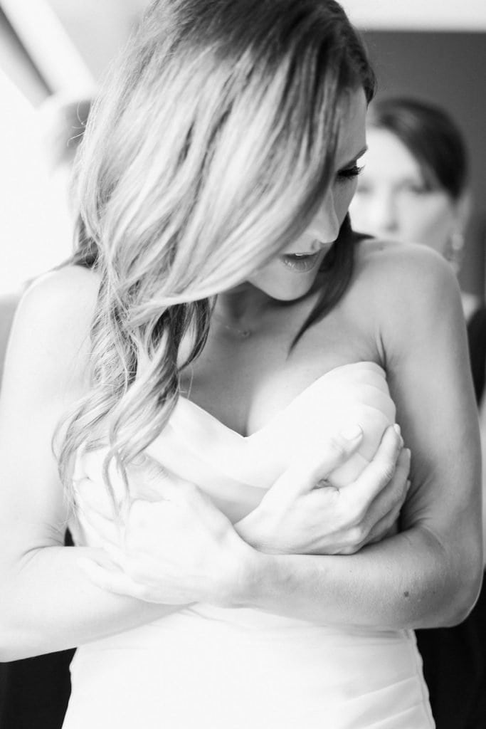 Bride getting zipped into her dress in black and white photo