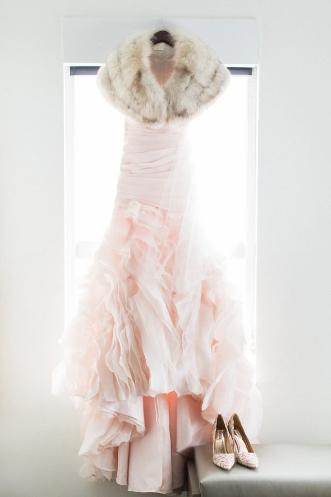 Photograph of blush pink wedding dress hanging in hotel room with fur shawl and badgley mischka bridal shoes