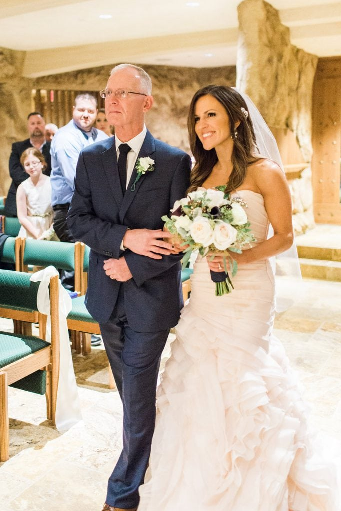 The bride being walked down the aisle by her father in the grotto of the Saints John and Paul Roman Catholic Church