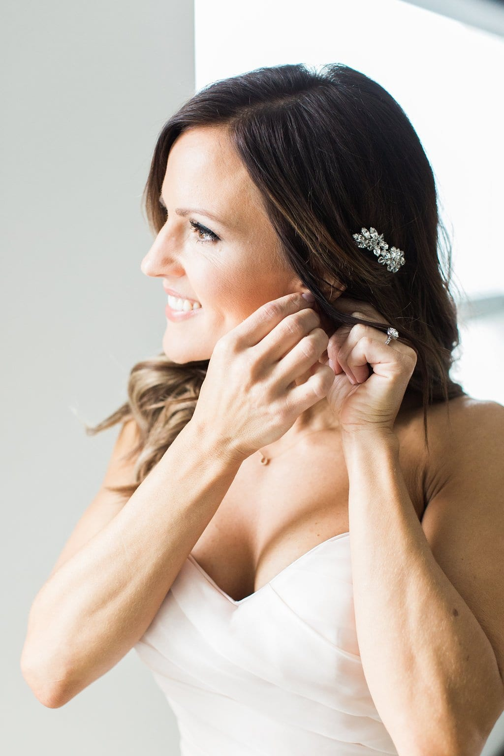 Photograph of the bride putting on her jewelry and earrings while getting ready