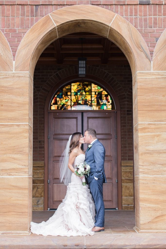 Photograph of the bride and groom kissing in the archway outside Saints John and Paul Roman Catholic Church