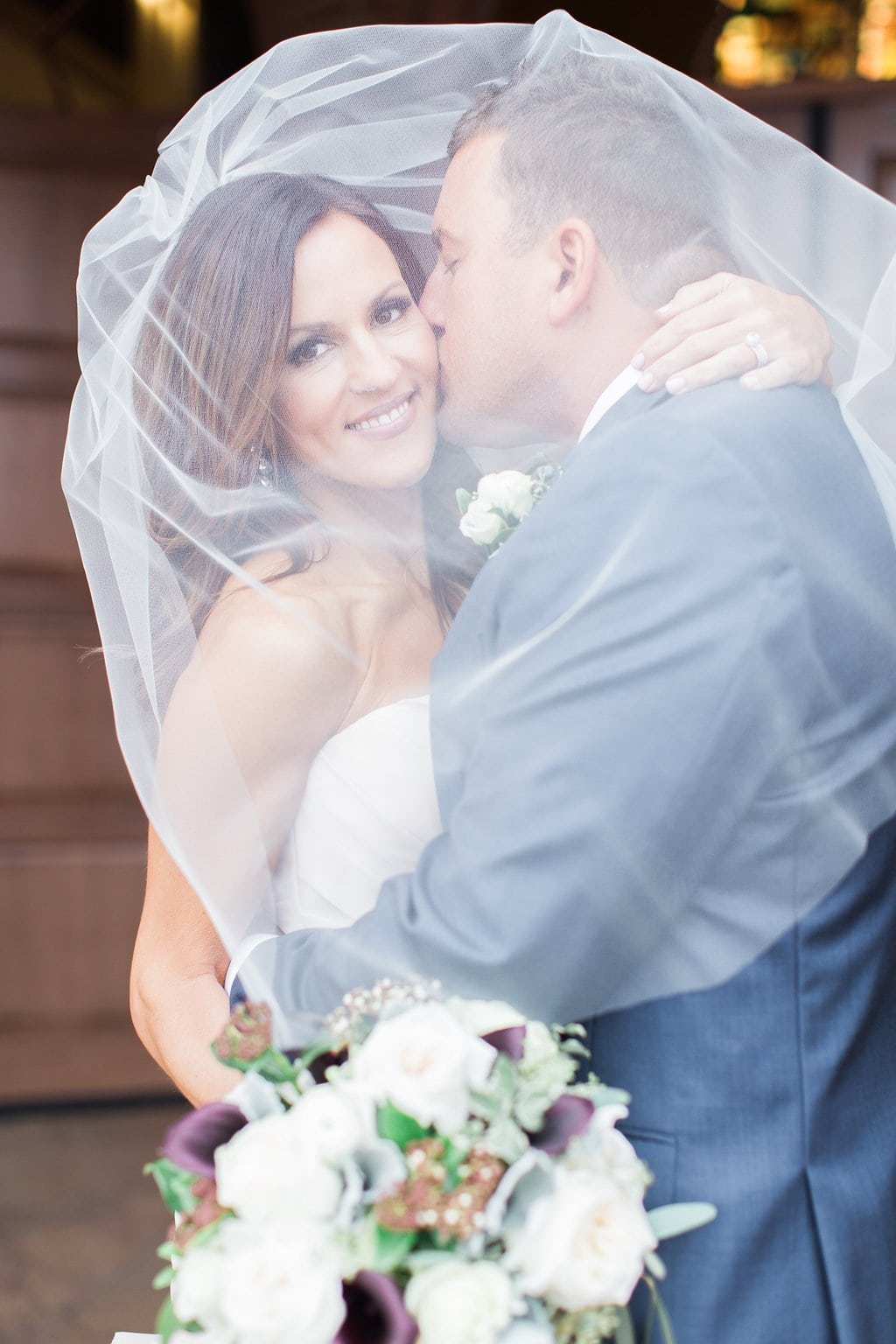 Photo of the groom kissing the bride's cheek under her veil outside the church