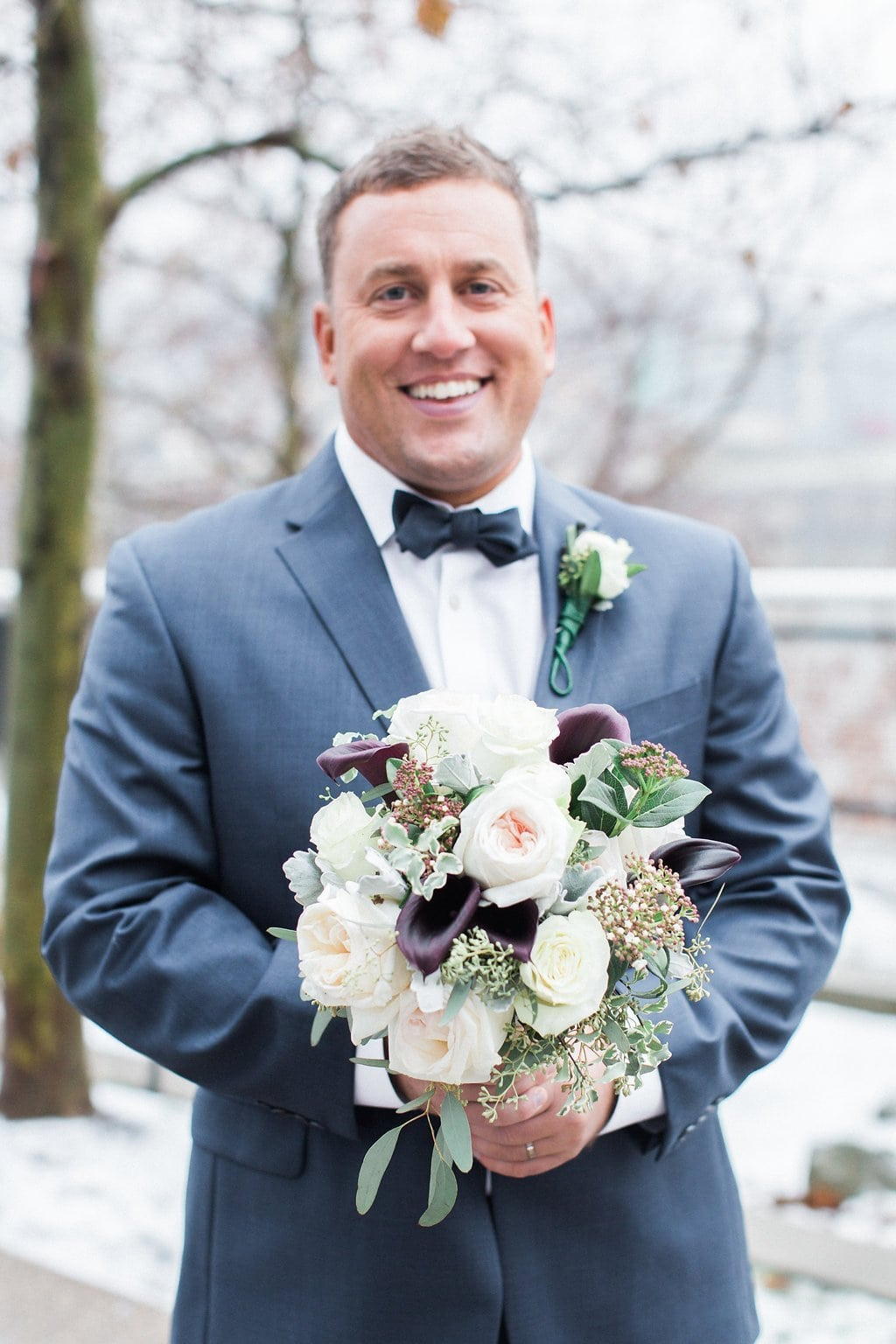 Photo of the groom holding the bride's bouquet