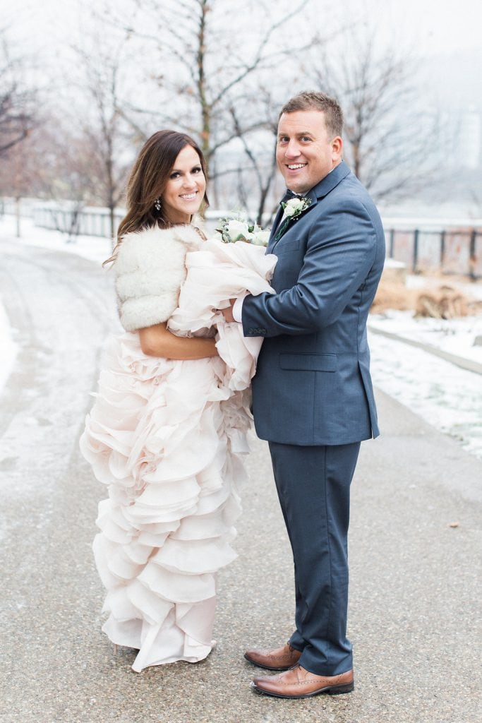 Portrait of the groom holding the bride's dress in the snow during their Pittsburgh winter wedding at J. Verno Studios