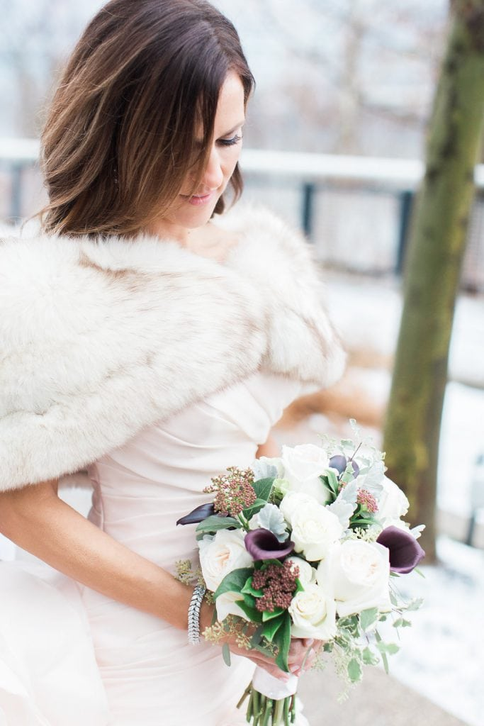 Photo of the bride out in the snow with fur shawl and bouquet