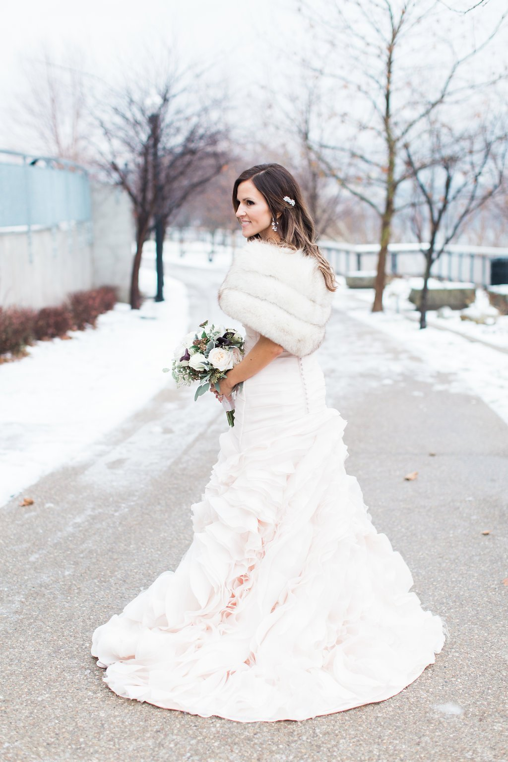Bride wearing blush pink wedding gown in the snow