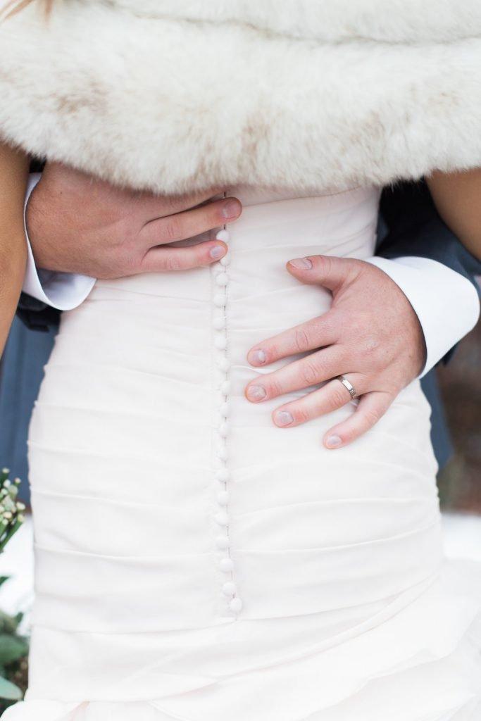 Portrait of groom grabbing bride's waist showing wedding ring