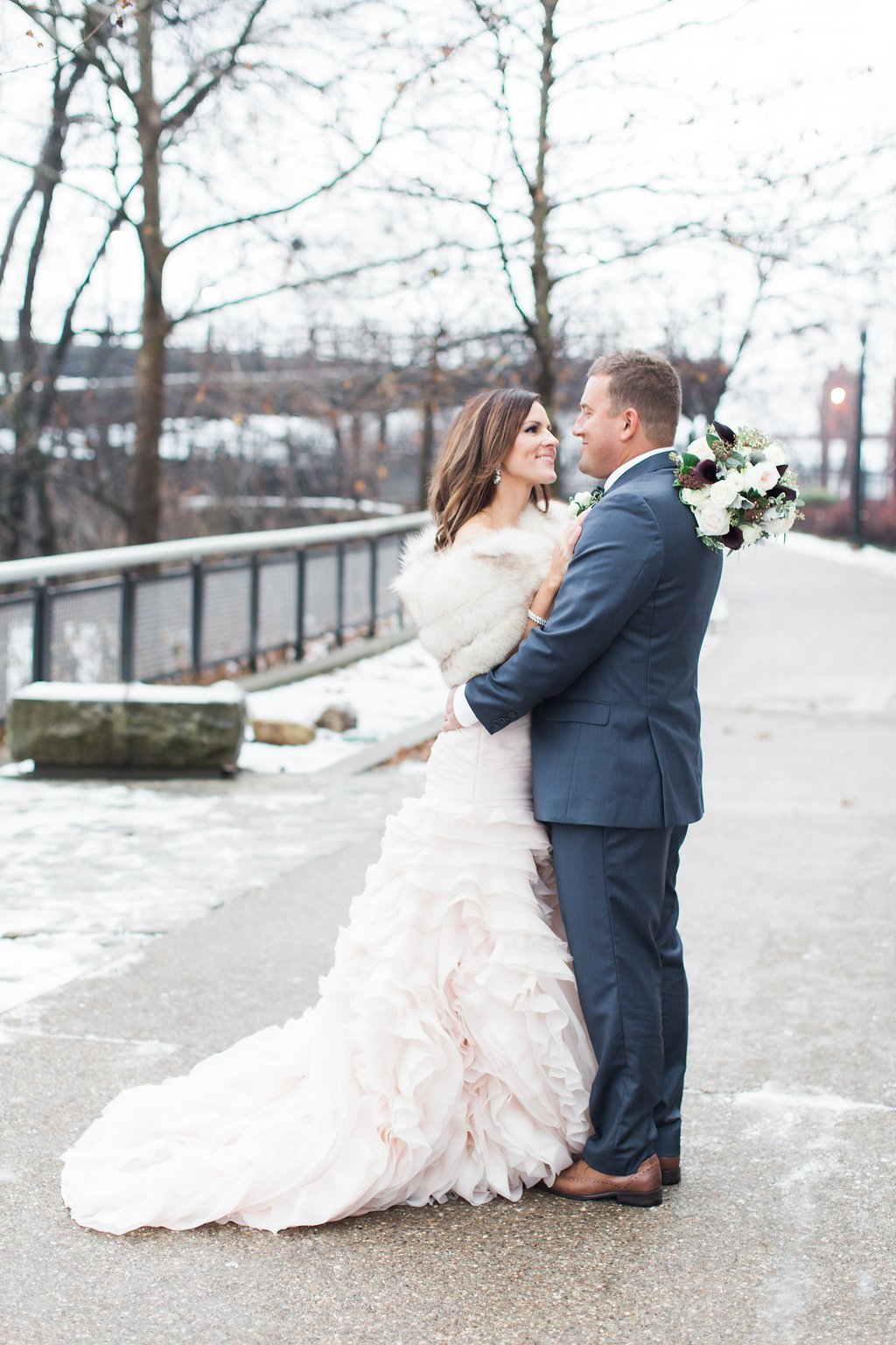 Bride wearing a blush pink wedding gown and fur shawl groom in navy blue suit