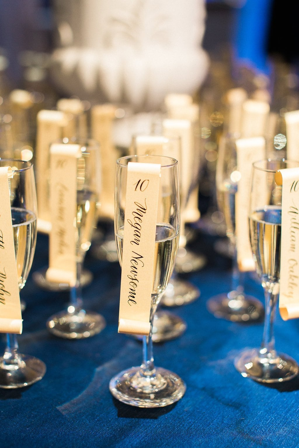 Calligraphy escort scrolls sitting in glasses of champagne for guests at this winter wedding