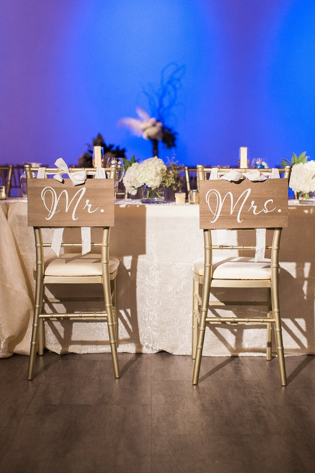 Calligraphy Mr. and Mrs. on wood signs over the back of gold chiarvari chairs with blue uplighting