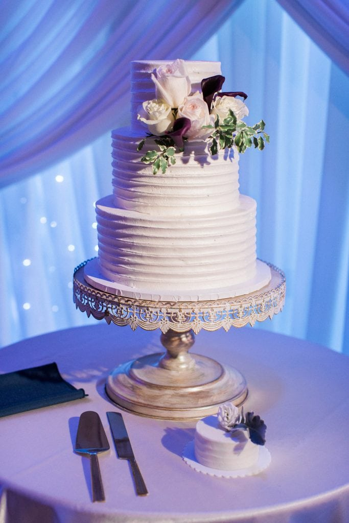 Simple white wedding cake with blush pink and purple accent flowers from Oakmont Bakery