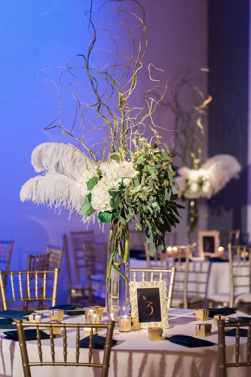 Tall floral centerpieces with white feathers and flowers at winter wedding reception