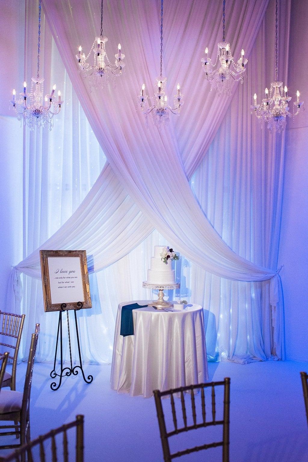 Wedding cake under chandeliers at reception
