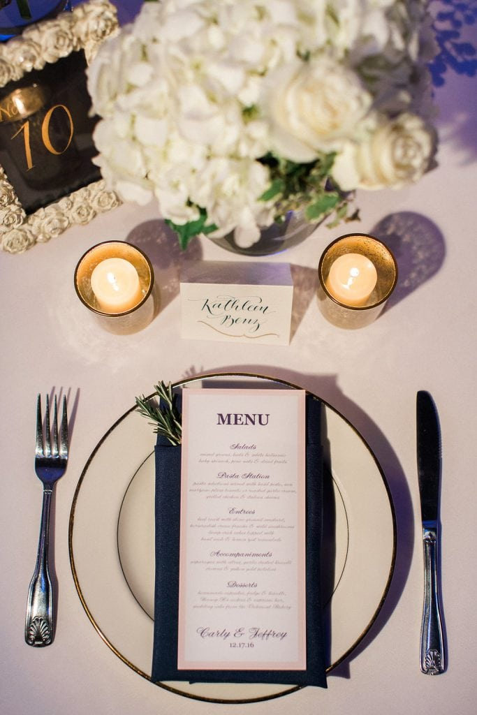 Table setting with calligraphy escort card, dinner menu, and a sprig or rosemary