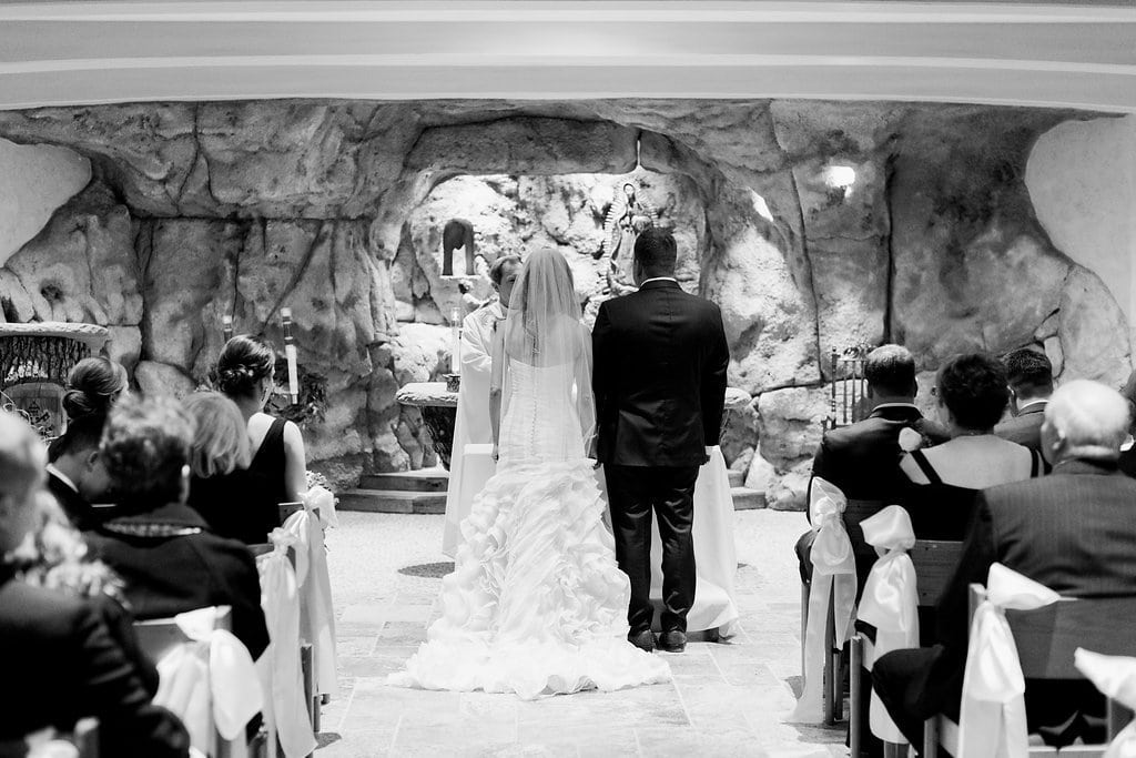 Black and white photograph of the bride and groom during their ceremony in the grotto - J Verno Studios Winter Wedding