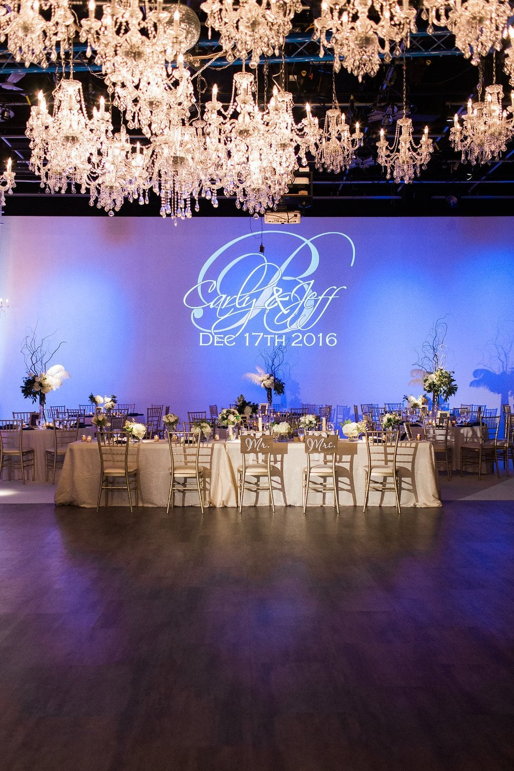 Gold and Navy blue accents with chandeliers and blue uplighting