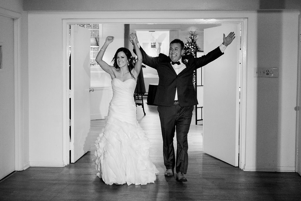 Bride and groom enter into their wedding reception holding hands in a black and white photo