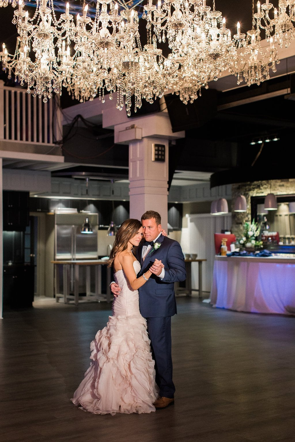 Bride and Groom sharing their first dance under the chandeliers