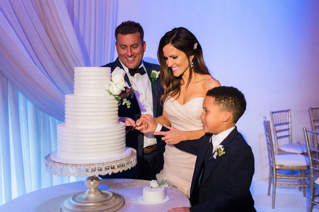 Bride and Groom cutting their white three tiered cake during their wedding reception at J. Verno Studios