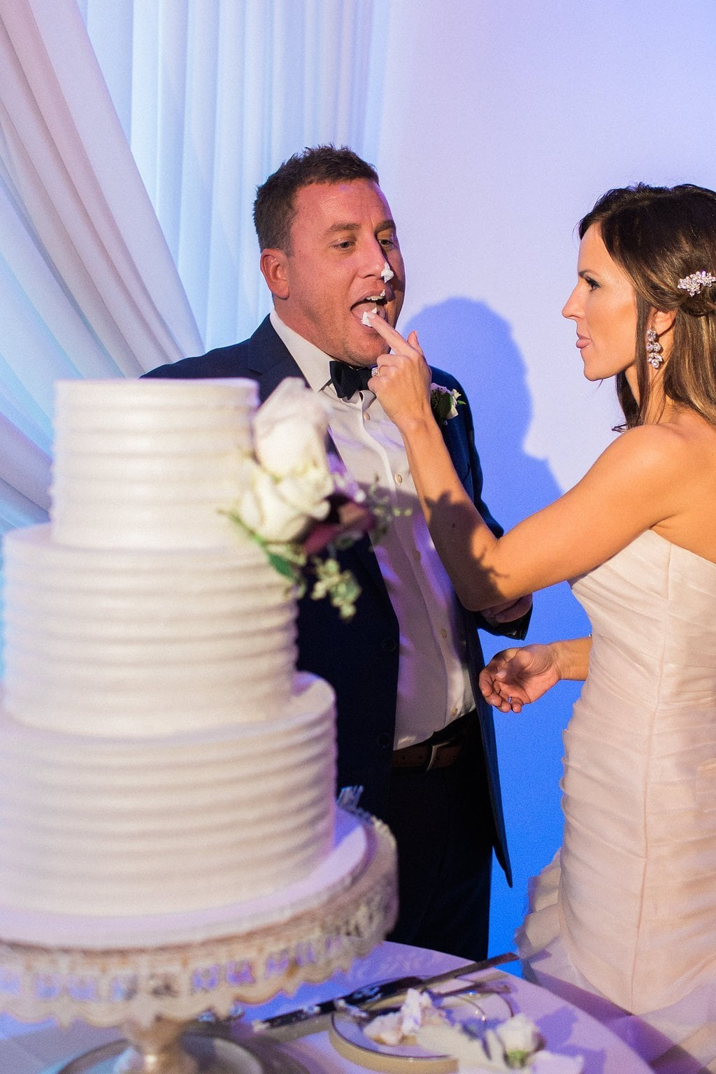 Bride and Groom cutting their wedding cake at their reception