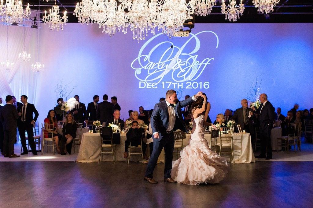 Bride and groom dancing under chandeliers at wedding reception