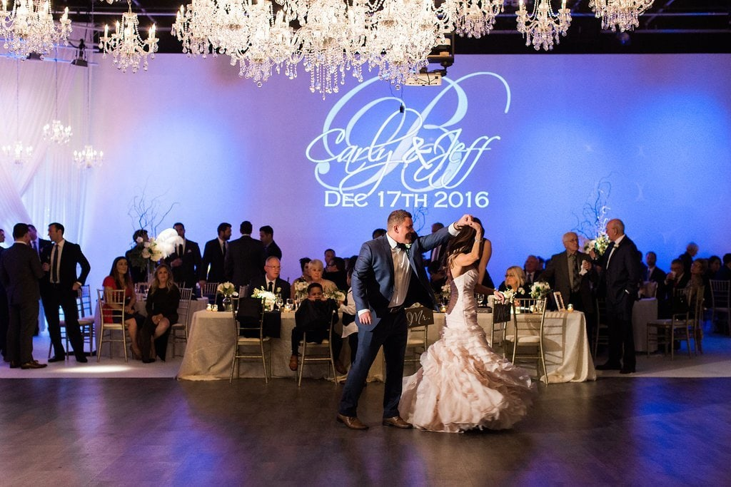 Bride and groom dancing under chandeliers at wedding reception