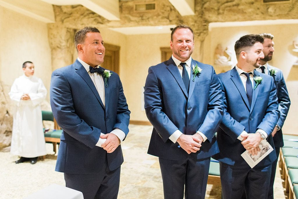 Groom seeing the bride for the first time walking down the aisle in the grotto of Saints John and Paul Roman Catholic Church