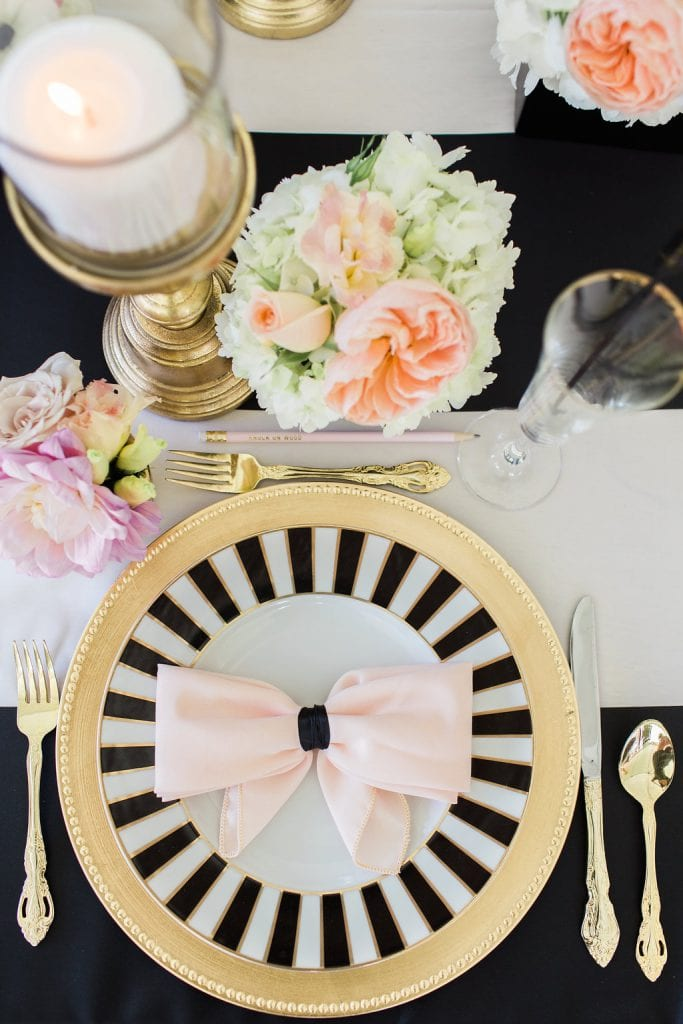 place setting with candles and flowers with black and white kate spade plate and gold accents