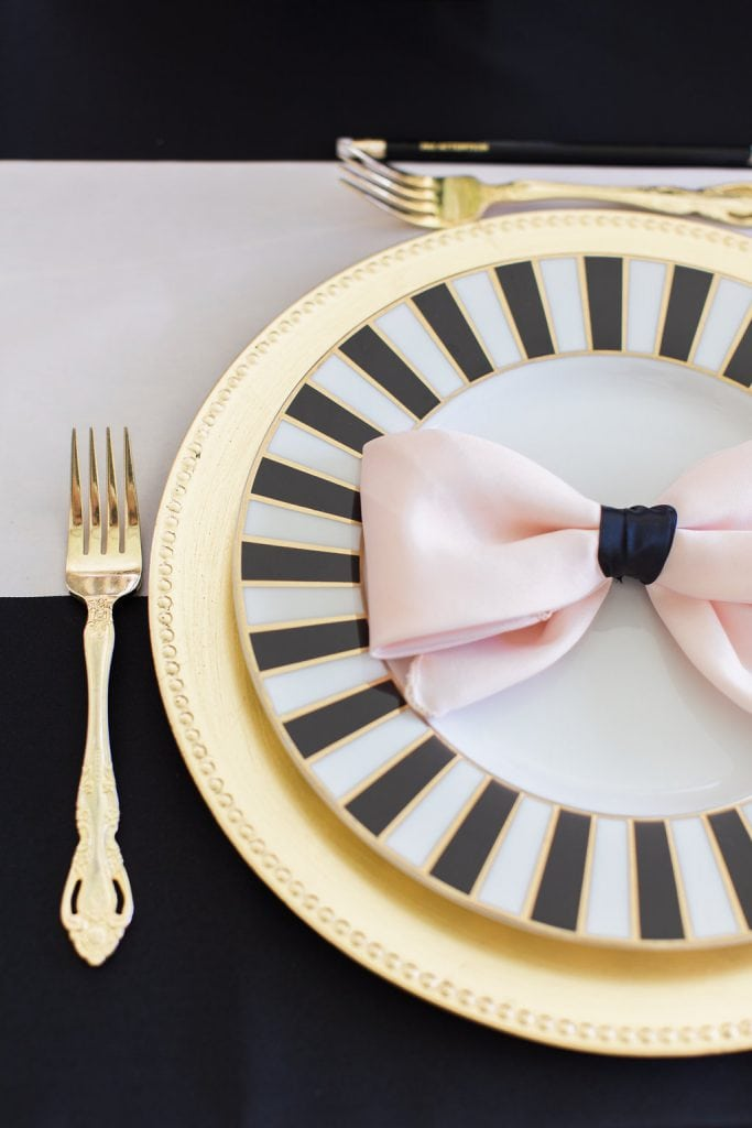 black and white kate spade plate with gold charger and pink bow napkins